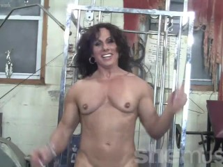 Mature female bodybuilder working only her muscles in the gym