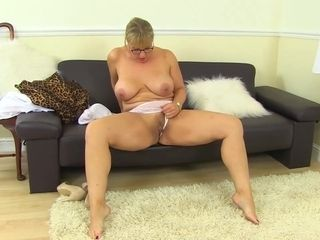 Mature blonde woman with glasses is masturbating on the couch, while she is alone at home